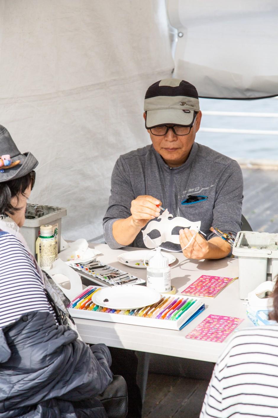 부스안에서 마스크에 색칠하고있는사진