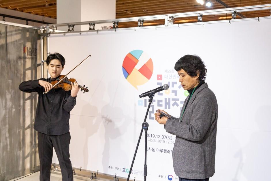 바이올린 연주자가 참가자에게 반주를 연주하며 노래부르는 사진